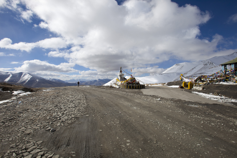 The crest of the pass is typically marked by a Chorten and fluttering prayer flags