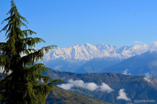 the awe-inspiring Great Himalayan Range far in the distance rippling above Dhauladhars