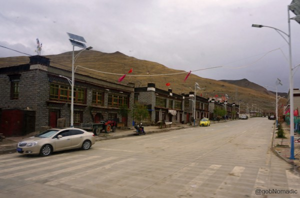 The main street of Kangmar; notice the Flag of China atop almost every building