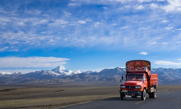 "Darchen - Manasarovar Lake - Paryang - Saga - Tibetan Plateau - Tibet Autonomous Region - China With jeep on the road. Western Tibet is remote, rugged, windy, and cold. It is much more rural than Central and Eastern Tibet. The people of this rugged area dress in long thick robes to protect themselves from the constant wind and cold. The woman all wear the distinctive fuchsia scarves around their heads. http://intothemiddlekingdom.com/2012/09/16/chiu-gompa-monastery-in-western-tibet/ We pass: Lake Manasarovar is a freshwater lake in the Tibet 940 kilometres from Lhasa. To the west of it is Lake Rakshastal; to the north is Mount Kailash. https://en.wikipedia.org/wiki/Lake_Manasarovar The Tibetan Plateau, is a vast elevated plateau in Central Asia or East Asia, covering most of the Tibet Autonomous Region and Qinghai Province in western China, as well as part of Ladakh in Jammu and Kashmir state of India. It stretches approximately 1,000 kilometres north to south and 2,500 kilometres east to west. With an average elevation exceeding 4,500 metres , the Tibetan Plateau is sometimes called ""the Roof of the World"" and is the world's highest and largest plateau, with an area of 2,500,000 square kilometres (about five times the size of Metropolitan France). Sometimes termed the ""Third Pole"", the Tibetan Plateau is the headwaters of the drainage basins of most of the streams in surrounding regions. Its tens of thousands of glaciers and other geographical and ecological features serve as a ""water tower"" storing water and maintaining flow. The impact of global warming on the Tibetan Plateau is of intense scientific interest."